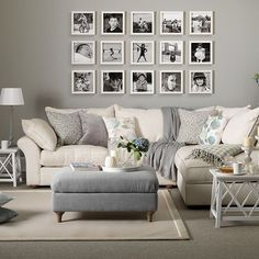 gray and white living room with family photo frames on the wall