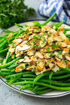 Green beans almondine on a serving plate, topped with toasted sliced almonds and chopped parsley. Green beans almondine on a serving plate, topped with toasted sliced almonds and chopped parsley. Quick Healthy Meals, Vegetarian Recipes Easy, Healthy Cooking, Nutritious Meals, Easy Cooking, Vegan Vegetarian, Yummy Recipes, Baked Garlic Green Beans, Oven Roasted Green Beans