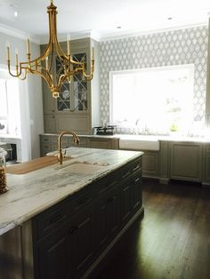 Exquisite kitchen features a burnished brass chandelier, Chart House 8 Light Mykonos Chandelier in Antique Burnished Brass, illuminating a dark gray kitchen island topped with natural stone countertops fitted with a sink and gold gooseneck faucet opposite a built-in chopping board.