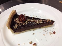 Chocolate tart topped with chopped pecans and a whole caramelised pecan