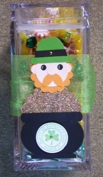 """Punch Art Leprechaun. A 1 1/2"""" strip of card stock runs down the back secured by brad in hat and brad in shramrock. Then a ribbon can run through it to tie on candy jar."""
