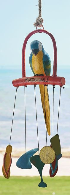 Perched atop a collection of Margaritaville inspired charms – including the lost shaker of salt – this handsome, hand-painted Parrot is ready to alert you to incoming breezes. | Margaritaville by Frontgate