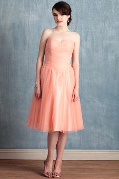 Cascading pintucks, raw hems, and a voluminous tulle skirt impart movement and texture to this elegant vintage-styled dress. Crafted in a soft pink hue with peach undertones, the dress is completed with a romantic sweetheart neckline, boning in the bodice, and interior bust cups for added comfort.