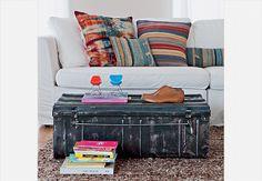 No lugar da mesa de centro convencional, ponha um baú, como o da foto, ou malas antigas empilhadas. Assim, você ganha espaço extra para guardar a bagunça