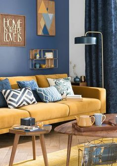 deco bleu et jaune, salon scandinave, canapé jaune moutarde, decoration murale en bois, mur couleur bleu foncé, parquet clair, tables basses en bois, lampe design