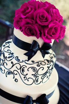 Fuchsia wedding cakes. Black, white, and bright hot pink. Your eyes go directly to the magenta rose topper on this scrolled and bowed wedding cake.