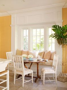 A window seat and a cozy upholstered cushion make this sunny banquette possible. Eye-catching trim and molding draw attention to the breakfast nook to set it off as the room's focal point. A trio of freestanding chairs provides more seating around the dainty wooden dining table.