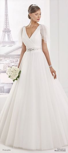 Tulle wedding dress, marked by high strassée belt size, feminine neckline, sleeves little tulle go with her skirt of tulle for an elegant and sophisticated bride.