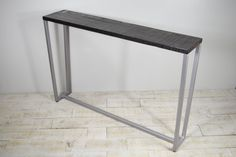 Another piece in the Belmont line, this entryway table is a clean addition to your space. The tapered steel legs support a white oak table finished in your choice of stain. The tables shown are in black stained oak with textured finish and smooth oak with Java finish. The table base is
