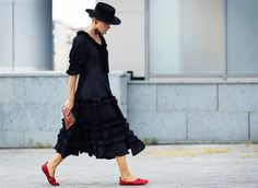 A black dress with ruffles is worn with a wide-brim hat, statement earrings, and red accessories