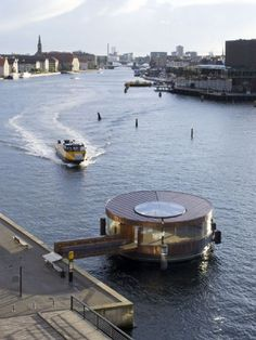 With the Opera Pavilion, which can accommodate 200 waiting persons, opera guests and other visitors to Holmen will have a place of shelter by the water bus quay.  In its form, the building takes its cue from the existing semicircle of the jetty. The pavilion thus has the appearance of a seamless, circular geometrical shape which is open towards the jetty and on two sides, as well as towards the gangway pier.  The clear, simple expression is underlined in the facade structure, which consists…