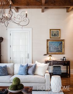 A delicate filigreed chandelier — a trademark of French cottage style — is a romantic counterpoint to the modern sofa. | Design: Benoit Gérard and Alexandre Blazys Photo: Adrien Williams