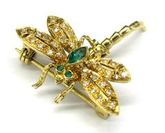 Ladies 18kt yellow gold diamond and gemstone dragonfly estate pin. Pin contains 2 round cut emeralds, 1 marquise cut emerald, and 28 round cut diamonds weighing a total of approximately .15ct.