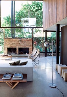 Argentinean materials, a roiling economy, and a pinch of personal tumult served as the recipe for furniture designer Alejandro Sticotti's Buenos Aires oasis. The living room resembles a Sticotti furniture showroom: The architect designed the couch, coffee tables, and stumplike stools. The fireplace is made of stacked stone from San Juan, a nearby province. Photo by Cristóbal Palma.