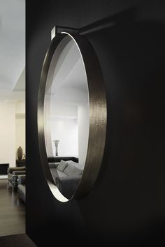 "Moi Mirror designed by Soraya Osorio. The bronzed steel support inserts into the wall, giving this sculptured piece the illusion of floating in midair. Dimension: 36"" Diameter  x 2 1/2"" Depth x 2"" Airspace Finish on Mirror Frame: Grazed Aged Brass  