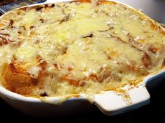 French Onion Soup Casserole - Slice thinly three large sweet onions. Sautee in 2 T olive oil until lightly browned. Layer in sprayed 2 qt casserole pan with 1 c shredded Swiss cheese.  In bowl whisk to blend 1 can cream of chicken soup, 2/3 c milk, 1 tsp soy sauce, fresh ground pepper.  Pour over onions. Top with 8 slices buttered French bread. Bake 350 for 15 min uncovered to toast bread. Remove and push bread slices under soup. Top with 1 c shredded Swiss and bake another 15 min.