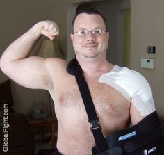 a big strong man powerlifter injured arm sling hairychest