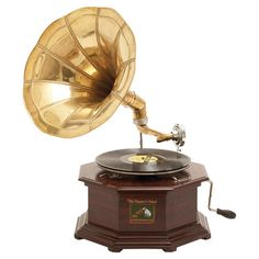 "HOME DECOR – ART – ACCENT – Classic gramophone with a polished wooden box and brass-finished, traditional horn.  Product: Gramophone statue Construction Material: Wood and metal Color: Brown and brass Features:  Traditional record player design Enhances any décor  Dimensions: 22"" H x 17"" W x 13"" D"