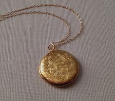 A beautiful, large, (29mm -or just under 1 1/8) round, brass locket with a lovely Victorian poinsettia floral design is suspended from a delicate gold filled chain. A beautiful classic. There is room inside for two photos. Photo size 20 or 6/8) Please select your desired chain length at checkout. You necklace will arrive beautifully gift wrapped.  The model pictured is wearing an 24 length chain.   ***To enter my Etsy shop, click here: https://www.etsy.com/shop/TangerineDesignEtsy