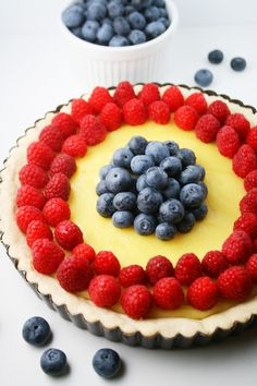 Fresh berries nestled on an almond custard filling with a homemade cookie crust. Perfect for a dinner party. #raspberrytart #blueberries Recipe on MomLovesBaking.com