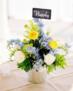 """Steel buckets of roses, hydrangeas, craspedia, delphinium, salidago, and freesia topped with chalkboard signs reading """"happily,"""" """"ever,"""" and """"after"""""""