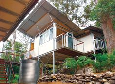 A photo of a house that uses lightweight steel framing, built on stilts on a sloping block.