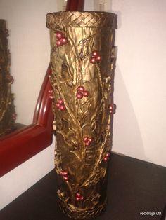 un jarrón hecho con tarros metálicos forrado y decorado con papel periódico.