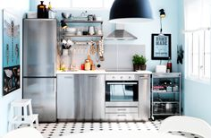 A stainless steel kitchen with a fridge-freezer on the left hand side, cupboards in the middle and an oven with hob and hood on the right. Extra wheeled storage is in the corner with stainless open shelving above the worktop.