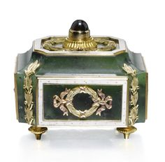 A Fabergé nephrite bellpush with gold and enamel mounts, Moscow, circa 1895 rectangular with incurved edges, the sides and top applied with laurel-chased ribbon-tied wreaths within dotted white enamel borders, cabochon garnet pushpiece, the corners with laurel and berry trails.
