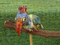 Bunter keramik Kakadu ho385  Ein bunter Tropenvogel, Kakadu oder auch Papagei sitzt hier auf einem Ast einer Weinrebe.    Er macht sich ganz besonders am Ast in einem Blumentopf.  Man kann ihn aber auch in einen Sockel (Loch ca 8 mm) stecken und am Tisch Schreibtisch stellen.    Der Kakadu ist natürlich völlig freihand aus Steinzeug Keramik Masse geformt und hochwertig bunt glasiert.