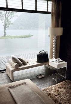 interior design: bedroom sitting area leather tufted bench seat, white side table, white floor lamp, throw blanket, shaggy floor rug