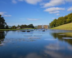 Chatsworth House and the Emperor Fountain from across the Canal Pond in the Peak District National Park  #architecture #blue #britain #canal #chatsworth #district #emperor #england #fountain #house #landscape #national #outdoors #park #peak #pond #scenic #sky #still #trees #uk #water