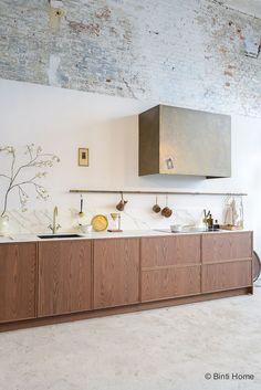 Vtwonen keuken in donker eiken met een gouden kraan en marmer look werkblad