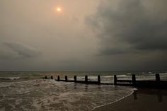 The sun shines through cloud as storm clouds turn the sky black over the sea front in Bognor Regis
