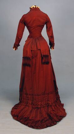SILK and VELVET BUSTLE DRESS with FRINGE, c. 1880. Claret ottoman with self piping, lace and crenelated trim at neck, bib front and cuff, floral cut velvet bodice and skirt front panel, draped SKIRT TRIMMEDIN CHENILE FRINGE and pointed pleats, crocheted buttons, polished cotton lining. B-30, W-22, skirt front L-37, back L-52. (Faint underarm stains, two buttons need to be resewn, waistband replaced, train relined and altered to button on to skirt hem) very good