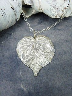 A beautiful lime silver leaf necklace, handmade using a real lime leaf. The leaf is handpicked and dried, painted with eco friendly silver clay, fired and soldered to a handmade wire bail, and then the whole item is polished by hand to leave a silver shine. It is finally finished