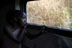 Faria takes in the sights as the train rushes towards Kimpese and she heads towards a new life in #Angola, land of her forebears.  ©UNHCR/B.Sokol