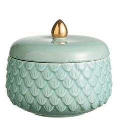Turquoise. Small box in glazed, textured stoneware. Matching lid with slightly crackled finish and a gold-colored knob. Diameter 5 in., height including lid