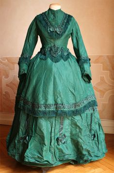 1868 dress in three pieces (bodice, skirt and tablier) in taffeta green, with applications in satin and green silk fringes. (link shows more views)