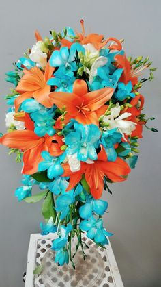 Fiji Blue Orchids,  White Freesia and Orange Lilies Cascade Bouquet. #orange #blue #flowers #tropicalflowers  Designed by Scarlett's Flowers.