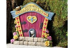 """""""Enter With A Happy Heart"""" fairy door with a small birds nest on top and a kitty welcoming you home. Note: This door does not open and close."""