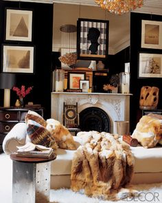 Walls are upholstered in Heritage velvet by Ralph Lauren Home, and the bed, upholstered in Ronda fabric from Brunschwig & Fils, is topped with a Ralph Lauren Home fox-fur blanket; the chair is by Carlo Bugatti.