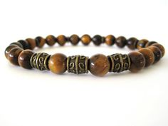 Masculine men's bracelet featuring 8mm Tiger Eye beads and gold tone pewter accent beads. A versatile bracelet that can be worn individually or stacked with leather wraps, a watch, other bracelets ... the options are endless!