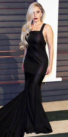 For the Oscars after-party, Lady Gaga traded in her voluminous custom Azzedine Alaia creation for a super sultry, vampy black gown with a dramatic train. Diamond jewelry and dark lip completed her look.
