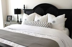 black headboard with grey and white bedding? Maybe a pop of color in a pillow?