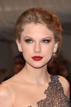 Taylor Swift Smoky Eyes - Taylor Swift added a smoldering touch to her vivid red lipstick with brown metallic shadow.