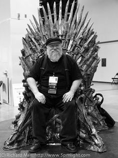 George R.R. Martin sitting the Iron Throne.