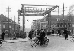 Dambrug over Leidse Rijn | 1937 | Vanaf Leidseweg. Zicht op de Damstraat. Het is druk, een verkeersagent is nodig