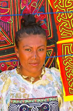 Kuna Indian woman (wearing Mola embroidery blouse, with Mola handicrafts in background), Wichub Wala Island, San Blas Islands, Panama
