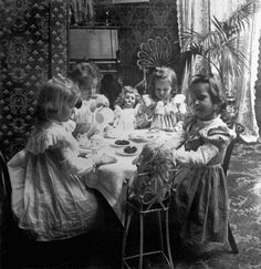 Girls in a parlor having a tea party with their dolls, 1905